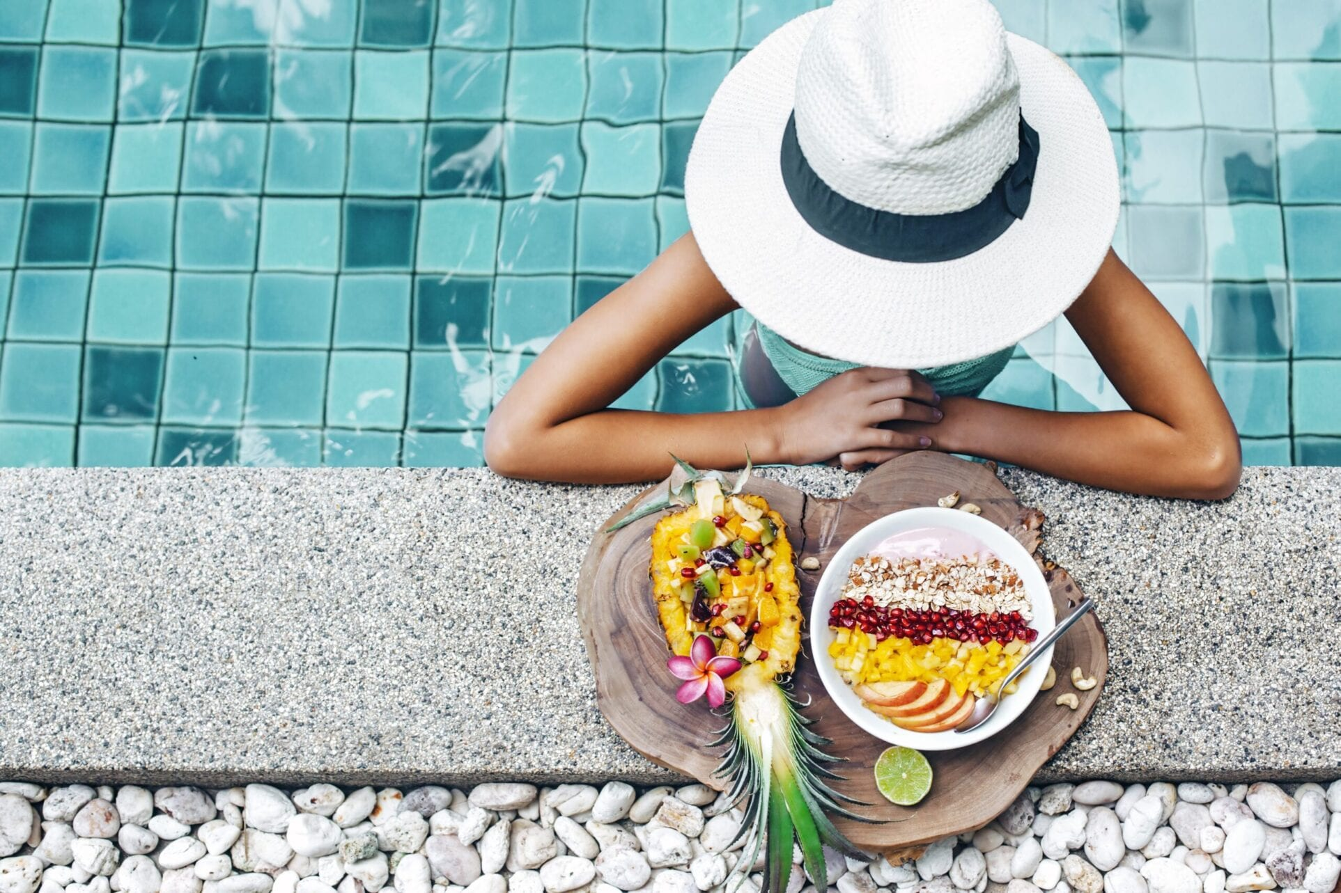 girl with fruit bowl in swimming pool